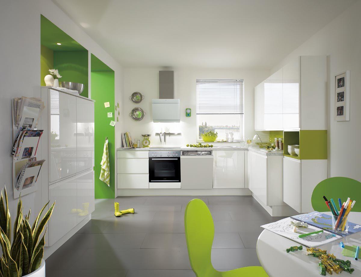Weiße Küche mit Griffmulden und grüner Rückwand. Foto: nobilia