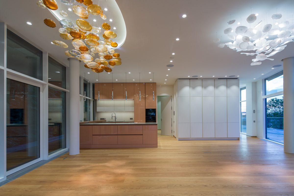 Design-Küche mit rosa (lachsfarbene) Fronten und zum Teil weißen Oberschränken und einer grauen Arbeitsplatte Foto: Schwab Küchen Salzburg