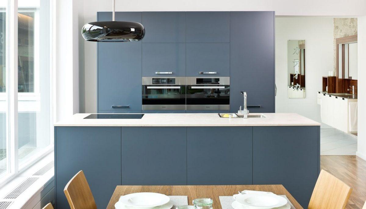 Blaue Küche mit schwarzem Dunstabzug und weißer Arbeitsplatte. Foto: Hase und Kramer; Foto: Hase und Kramer
