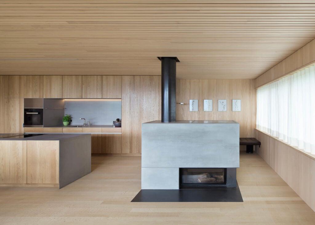 Wohnküche aus Holz mit offenem Kamin aus Beton Foto: Dietrich | Untertrifaller (Angela Lamprecht)