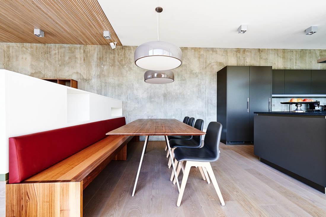 Küche mit einer Sitzbank aus Holz und roter Rückenlehne aus Leder. Foto: Billaudet
