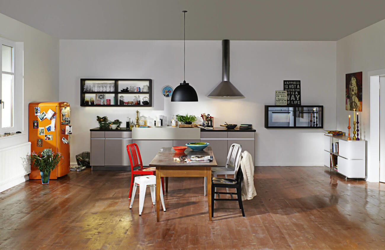 Kleine Küchenzeile mit buntem freistehendem Kühlschrank als Highlight