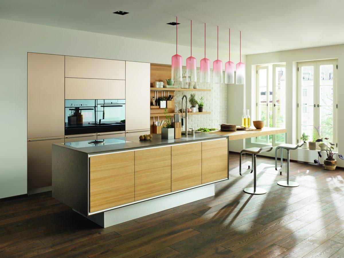 Moderne Küche aus Holz mit Insel und verlängertem Esstisch; Foto: Team7