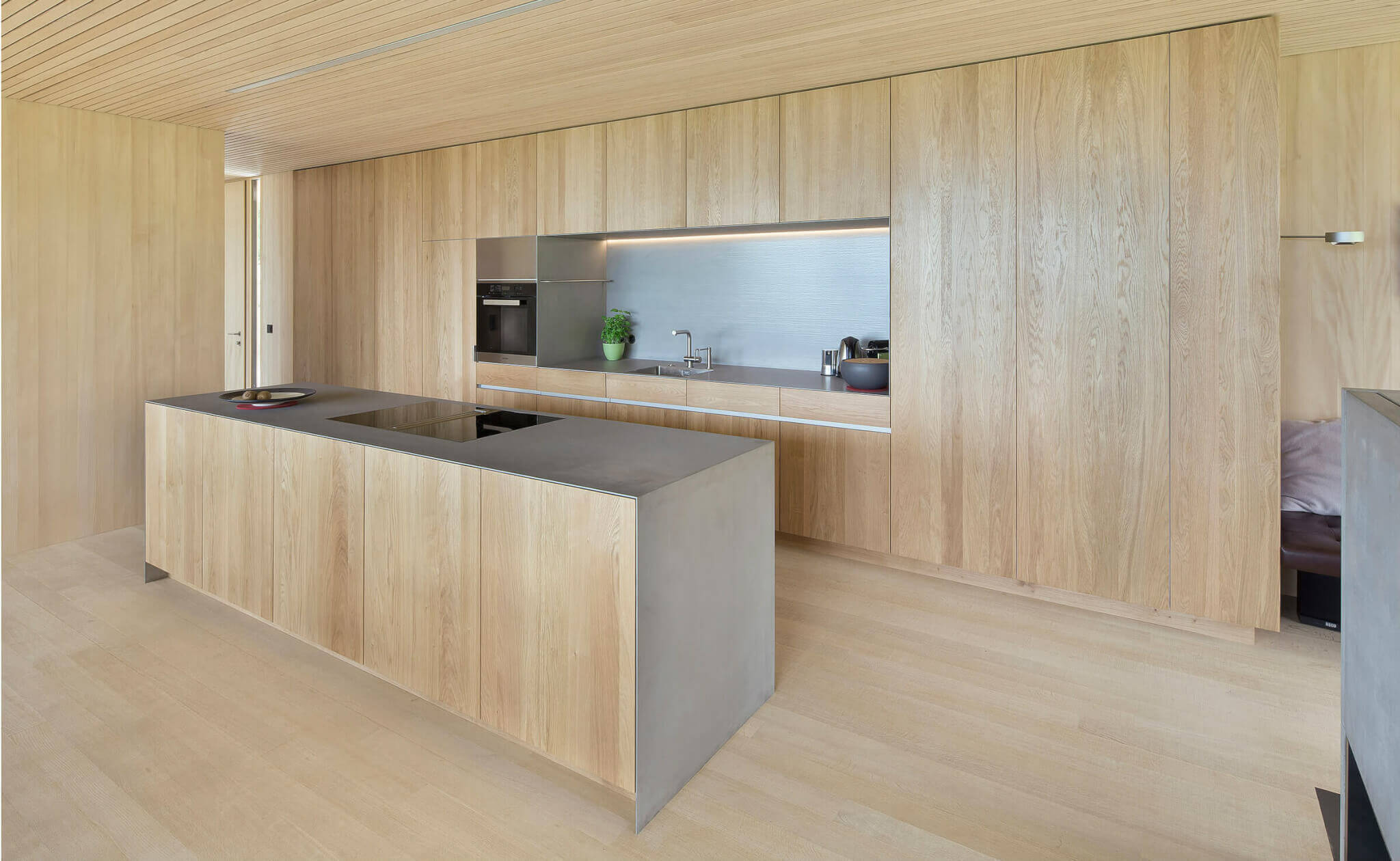 Küche aus Holz mit einer Kochinsel, dünne Arbeitsplatte aus Beton. Foto: Dietrich | Untertrifaller (Angela Lamprecht)