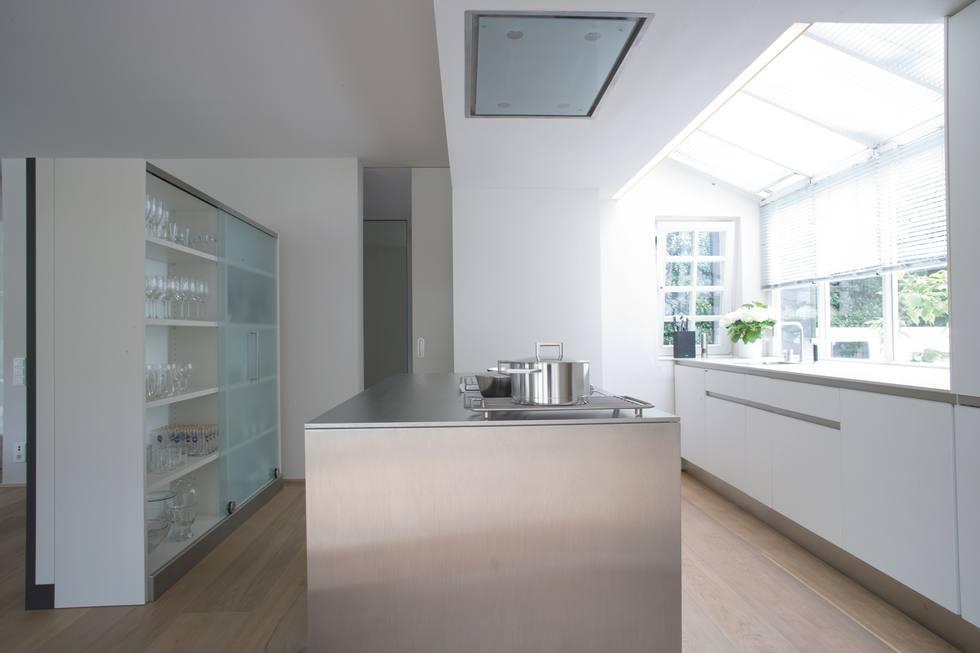 Weiße Küche mit Kochinsel und Arbeitsplatte aus Edelstahl; Foto: allmilmö