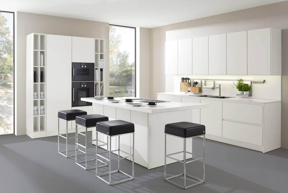 Weiße Küche mit Insel und modernen Barhockern; Foto: allmilmö