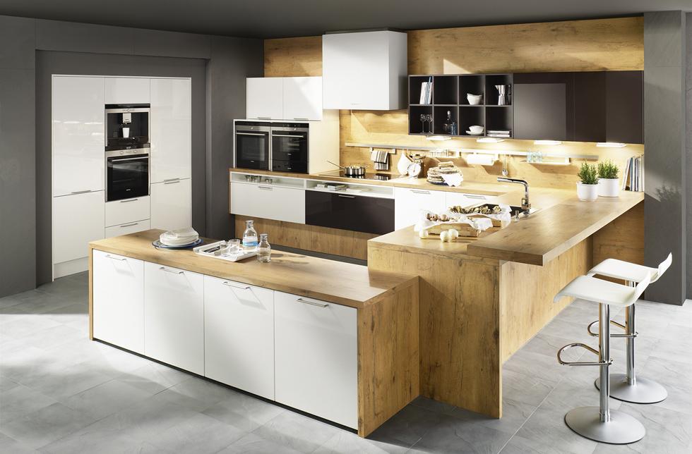 Moderne Hochglanzküche mit weißen Fronten und Bartheke aus Holz; Foto: Dan Küchen
