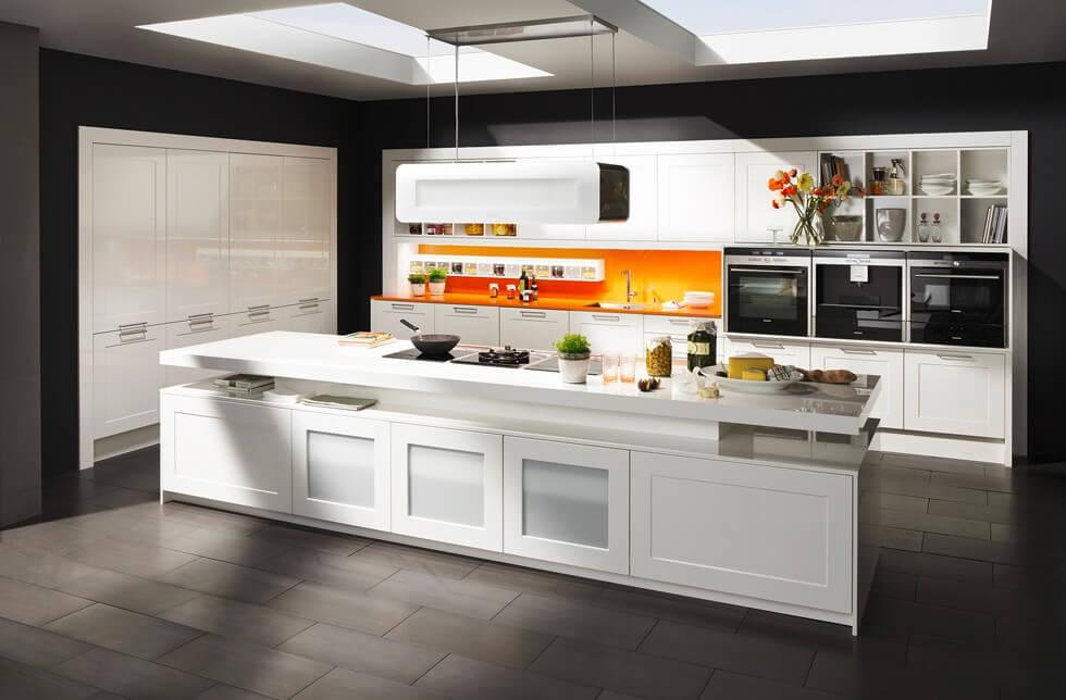 Leuchtend orange Küchenrückwand als Kontrast zur schwarz weißen Küche; Foto: DAN Küchen
