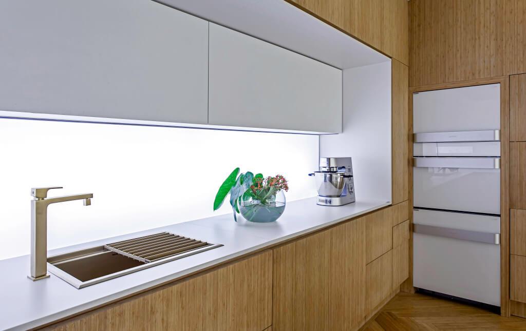 Weiße Küche mit Holzelementen und weißer Dekton-Küchenarbeitsplatte; Foto: Dekton Consentino