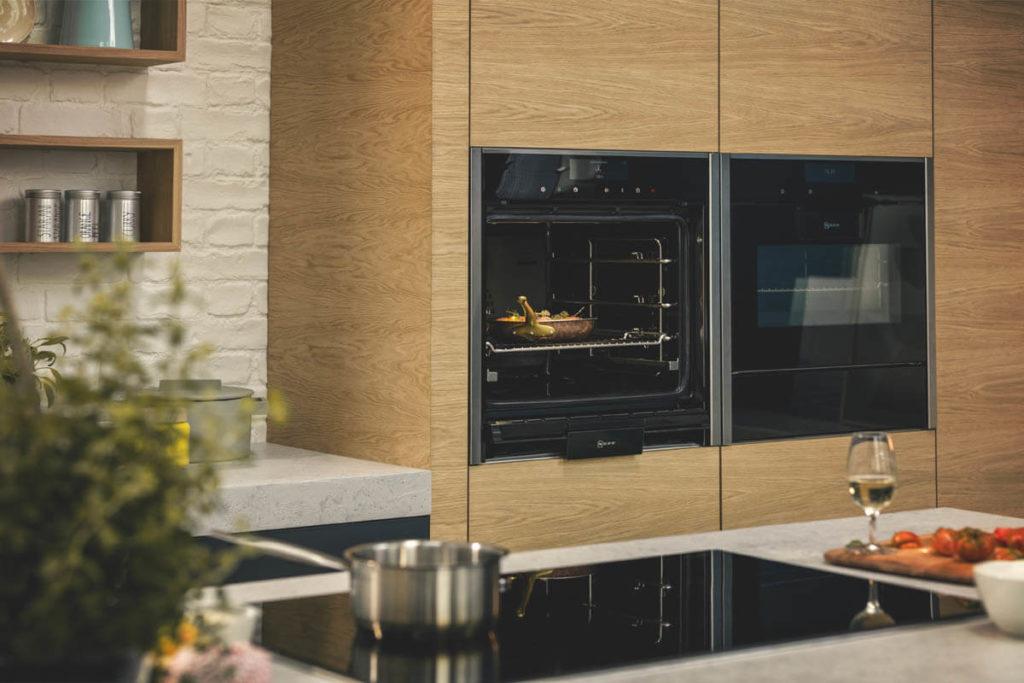 Moderner Backofen in Augenhöhe mit Kochfeld auf der Kücheninsel