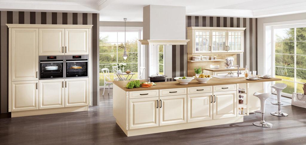 Landhaus Küche mit edlen Fronten in Magnolie, großer Kochinsel mit Arbeitsplatte aus Holz und modernen Barhockern; Foto: Nobilia