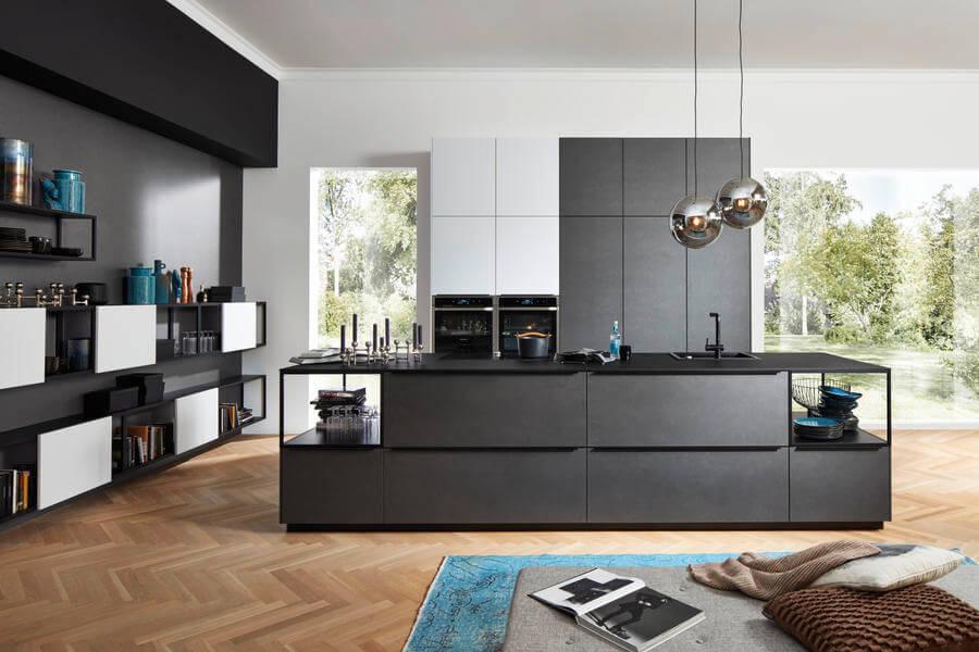 """Moderne Küche mit Kochinsel und Fronten aus Metall (Nolte Küchen Fronten """"Ferro Blaustahl"""" und """"Soft Lack Arcticweiß Softmatt""""). Foto: Nolte"""