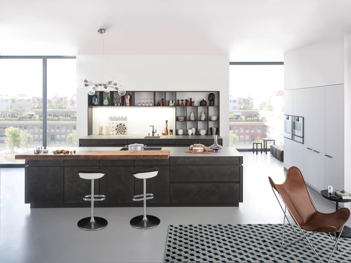 Leicht Küche mit dunklen, grauen Fronten in Betonoptik mit Kochinsel und Barhocker (Leicht Concrete-A) und Holztheke. Foto: Leicht
