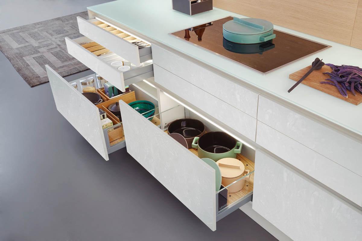 Weiße Küche mit hellen Fronten in Betonoptik und schöner Arbeitsplatte aus Glas (Leicht Concrete-C). Foto: Leicht