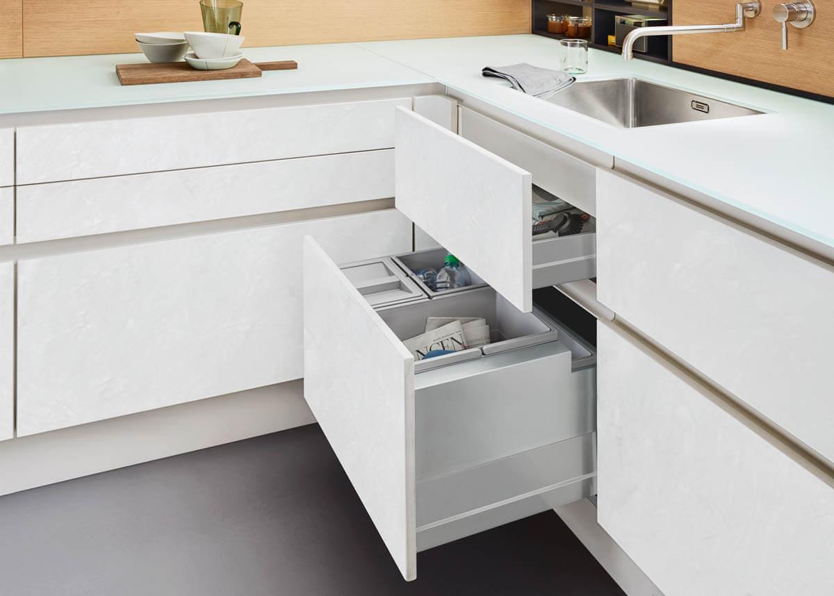 Helle, grifflose Küche in Weiß mit Fronten in Betonoptik und schöner Arbeitsplatte aus Glas (Leicht Concrete-C). Foto: Leicht