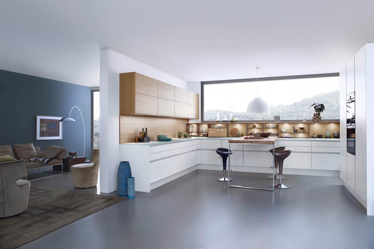 Weiße, grifflose Küche mit weißen Beton-Fronten und Oberschränken aus Holz (Leicht Concrete-C weß). Foto: Leicht