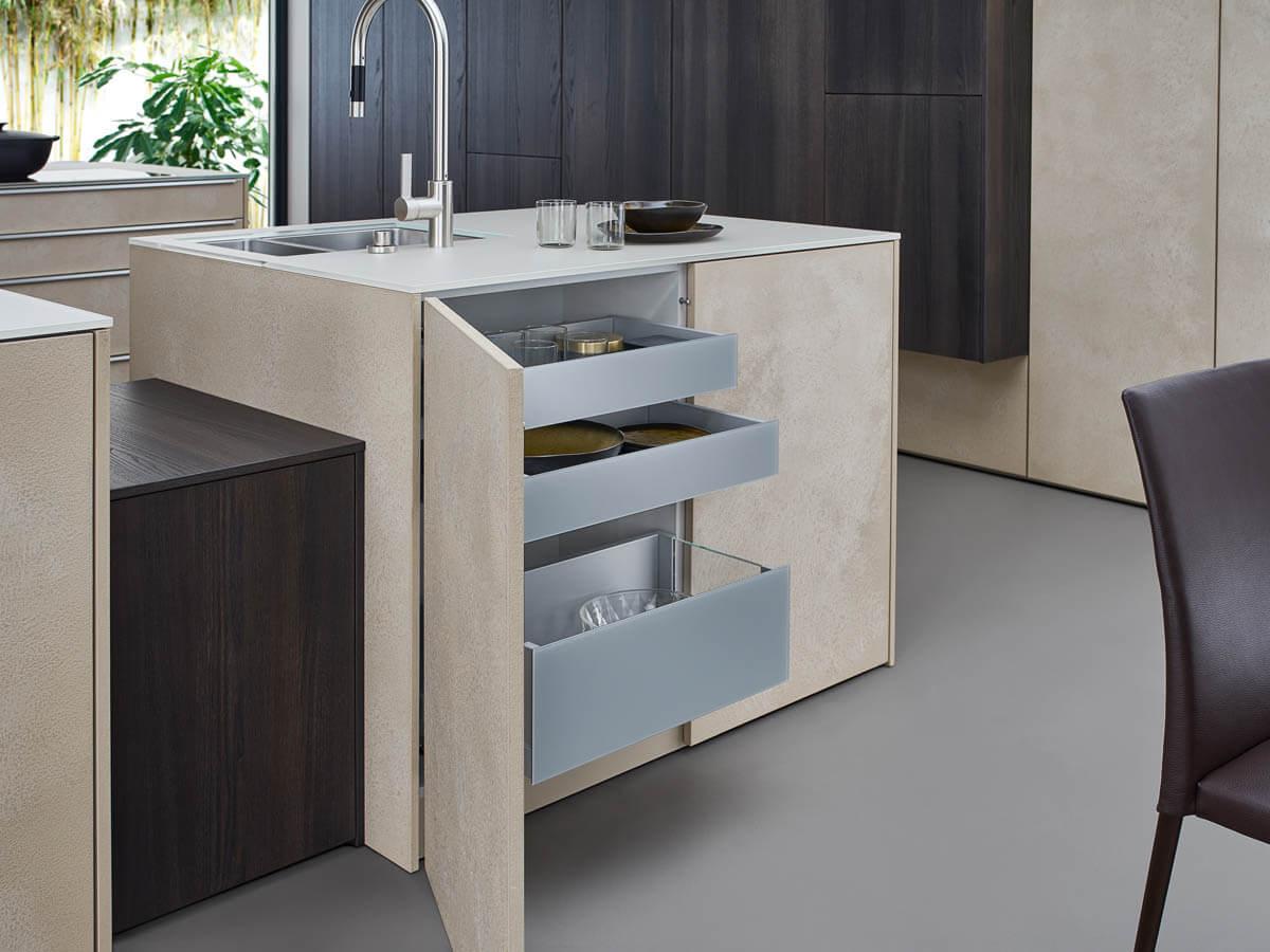 Helle, grifflose Küche mit Beton-Fronten in creme-beige (Leicht Topos Stone) dunkelgrauen Hochschränken. Foto: Leicht