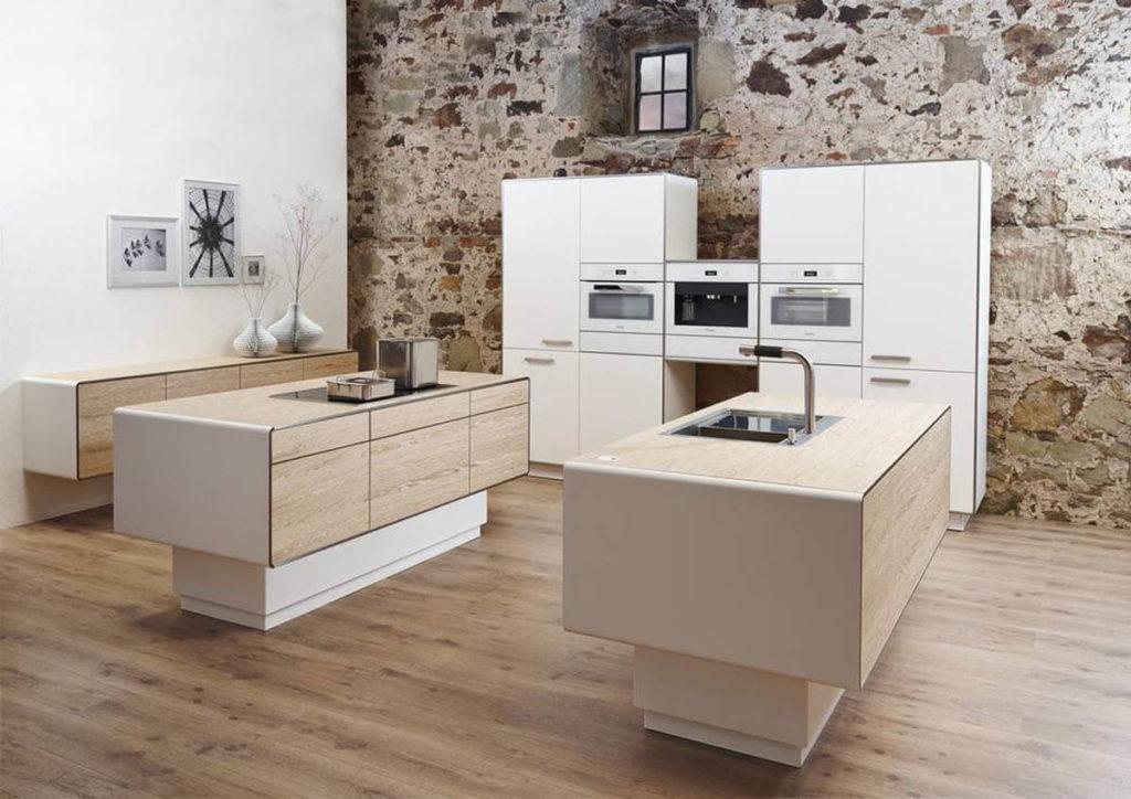 Diese Inselküche hat sogar zwei Kochinseln aus Holz (Eiche Furnier) und einer Zeile mit weißen Hochschränken (Diamantlack Weiß). Foto: Allmilmö