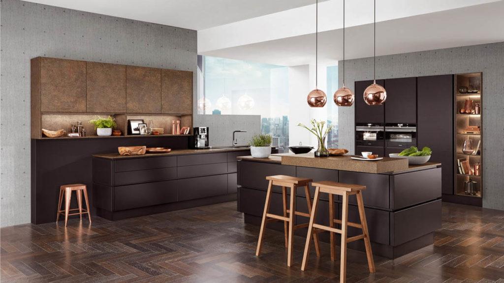Dunkelbraune, fast schwarze zweizeilige Küche mit Kochinsel von Nobilia. Die Hängeleuchten aus Kupfer sind die perfekte Ergänzung zu den dunklen Küchenfronten. Foto: Nobilia