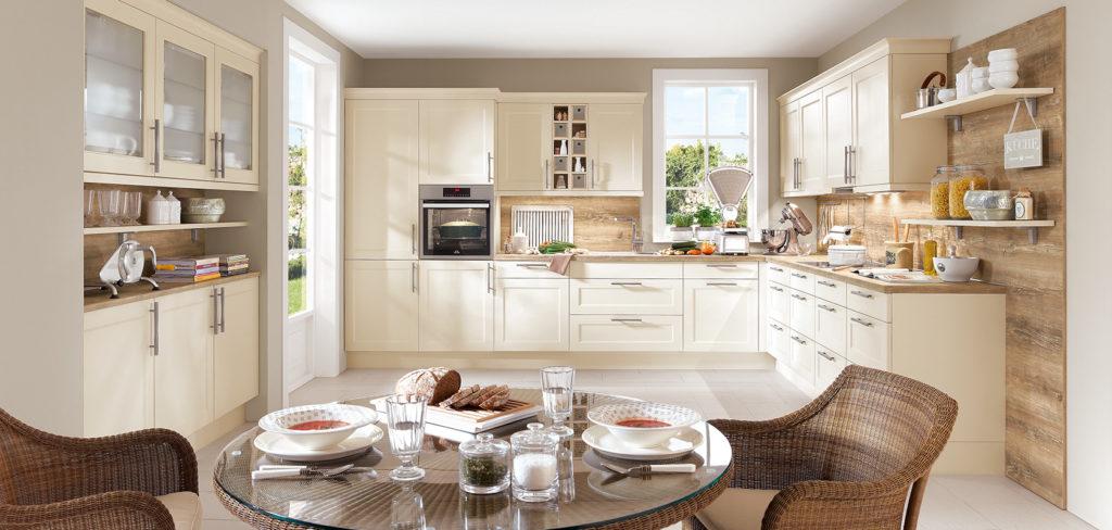 Küche in L-Form mit beigen Fronten, Arbeitsplatte aus Holz und passender Wandverkleidung; Foto: Nobilia