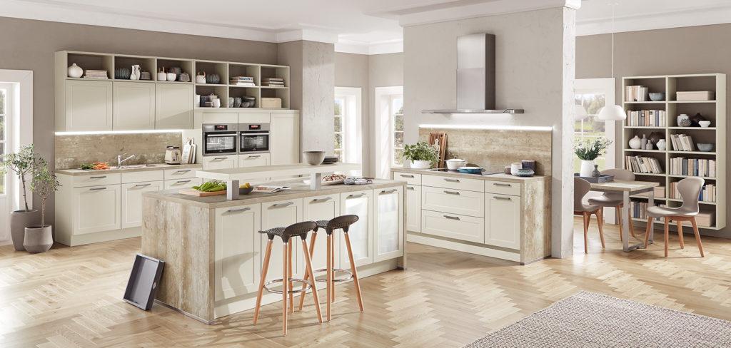 Küche mit Insel und zwei Küchenzeilen, Fronten mit Rahmen im Landhausstil und Arbeitsplatte in Stein-Optik; Foto: Nobilia