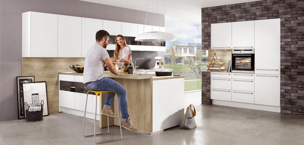 Küche mit Insel, grifflosen Oberschränken und weißen Fronten sowie dazu passender Arbeitsplatte und Bar-Theke aus Holz; Foto: Nobilia