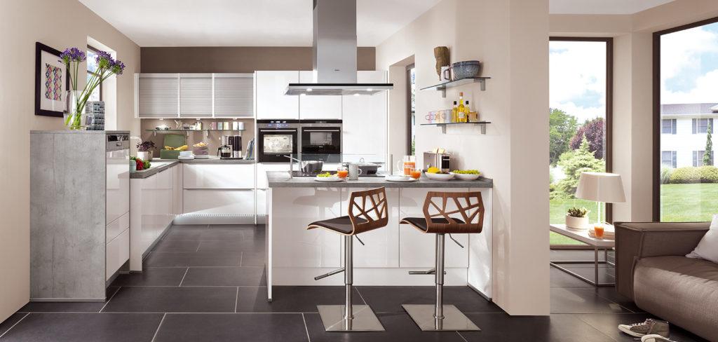 Küche mit Hochglanz Fronten in Weiß, kleiner Insel und Arbeitsplatte in Beton Optik; Foto: Nobilia