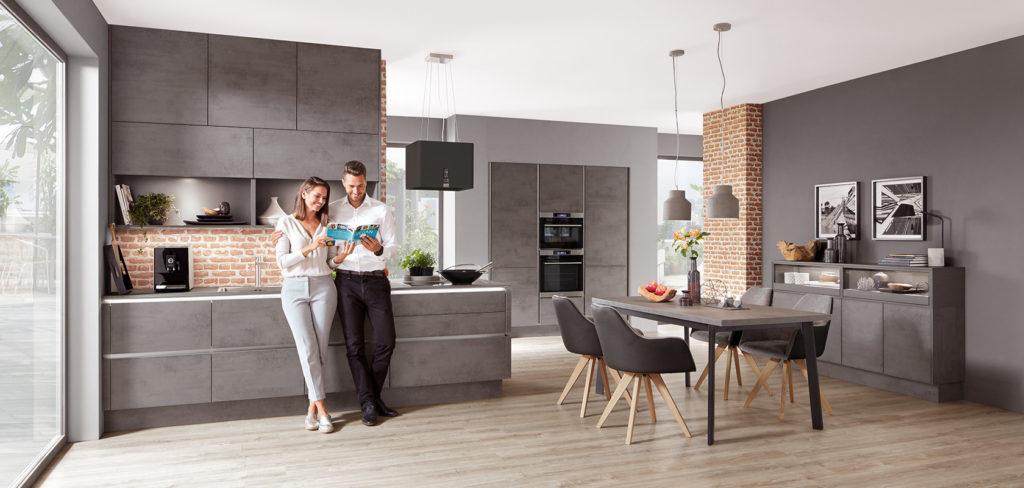 Beton Küche ohne Griffe mit Griffleisten in Edelstahl Optik und Edelstahl Arbeitsplatte; Foto: Nobilia
