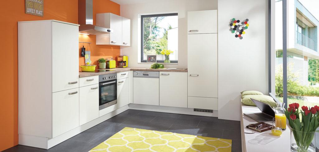 Weiße Küche in L-Form mit matten Fronten, Griffen und Holz-Arbeitsplatte; Foto: Nobilia