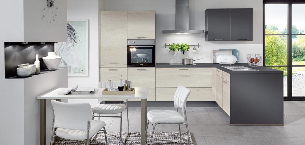 Küche in L-Form mit freistehender Insel, Lackfronten in Magnolia und dunkler Arbeitsplatte in Granit Optik; Foto: Nobilia