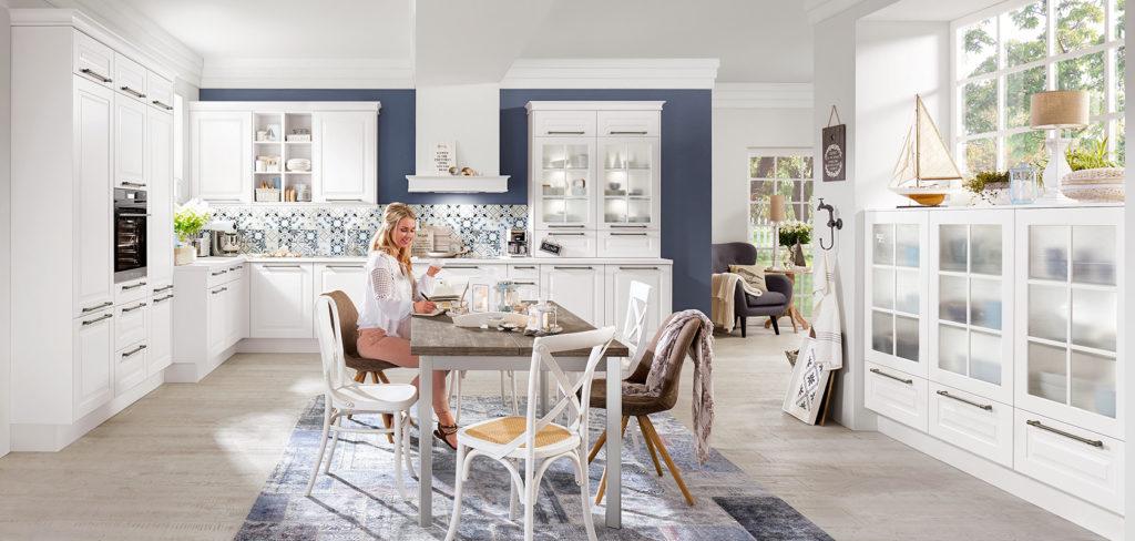 Weiße Küche im Landhaus-Stil und L-Form mit großem Hochschrank, weißer Arbeitsplatte und Edelstahl Griffen; Foto: Nobilia