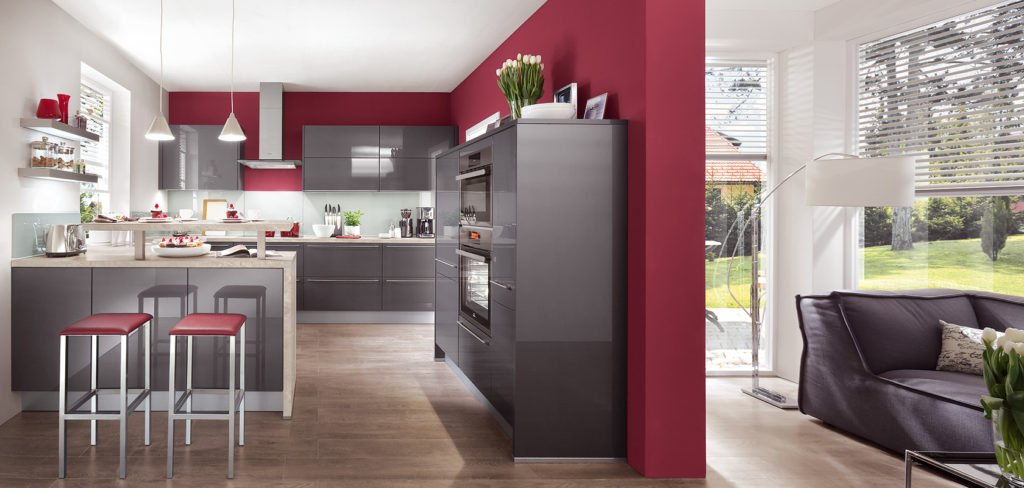 Küche mit dunkelgrauen Hochglanz-Fronten, Kücheninsel mit Holzarbeitsplatte und dunkelroter Wand; Foto: Nobilia