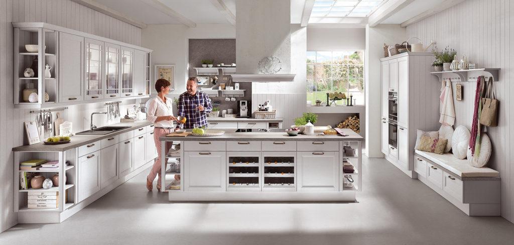 Küche mit Echt-Holz Fronten im Landhausstil, Kochinsel, offenen Regalen und passenden Griffen aus Stahl; Foto: Nobilia
