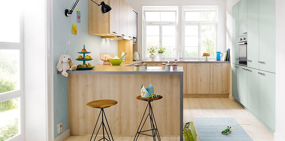 Grünstige Holz-Küche der Preisgruppe 1 mit Kunststoff-Fronten aus der Serie Bari Castell Buche in G-Form. Foto: Schüller Küchen