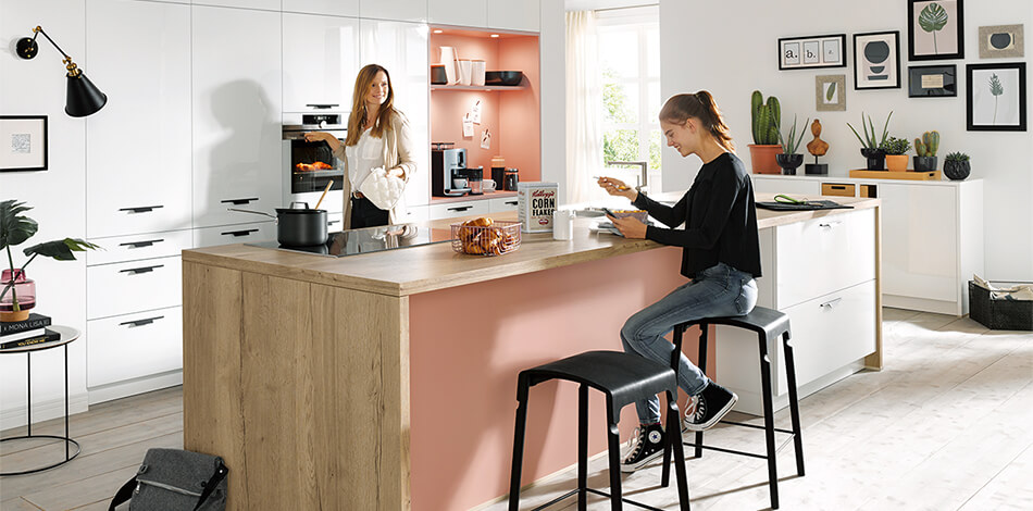 Schüller Küche mit Fino Fronten in Kristallweiß (Preisgruppe 3), UV-Lack hochglanz mit Kochinsel im Holz-Look und Akzentfarbe. Foto: Schüller
