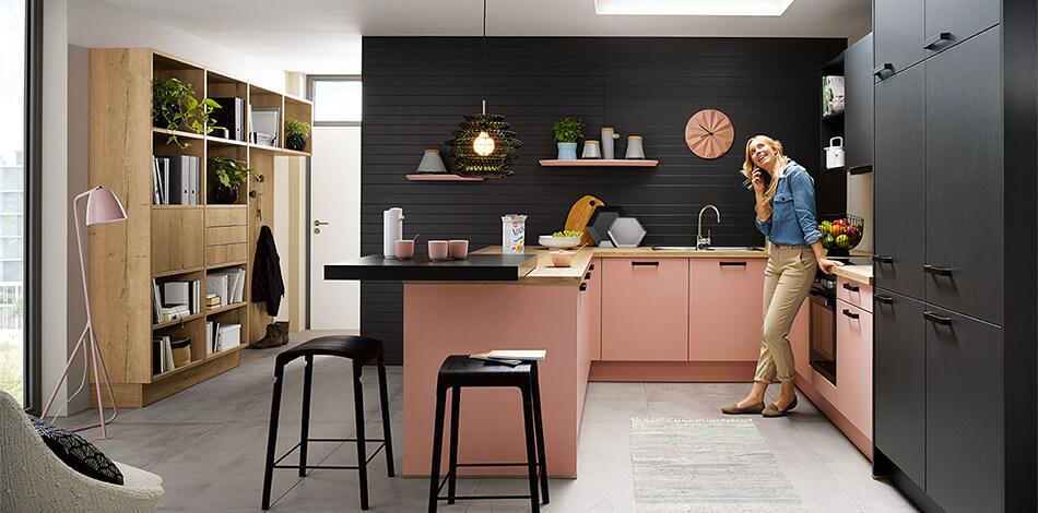 Schöne U-Küche von Schüller mit Biella Fronten in Pastellrose Satinlack matt (PG4) und schwarzen Hochschränken. Foto: Schüller Küchen