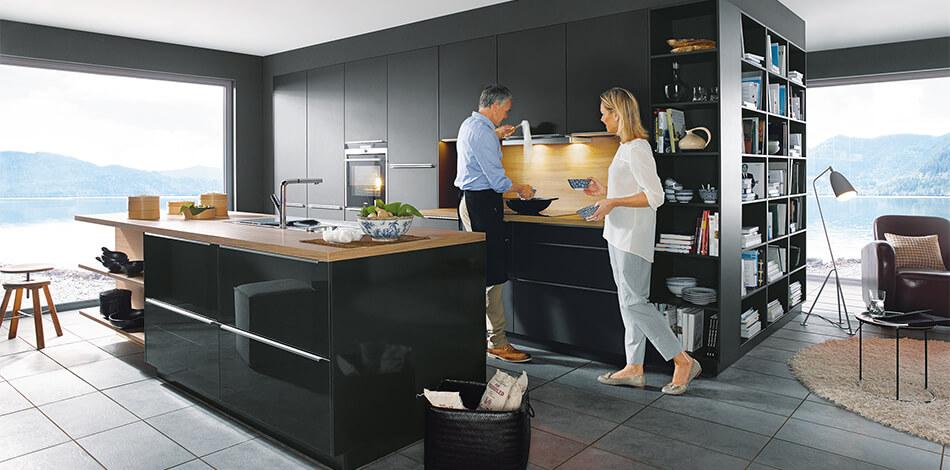 Moderne, schwarze Küche mit Glasfronten (Glasline Lavaschwarz Hochglanzlack, PG6) mit Arbeitsplatte aus Holz. Foto: Schüller Küchen