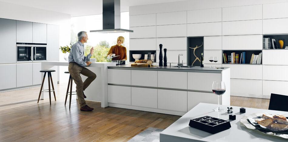 Klassische Küche mit weißen Echtglasfronten (Glasline matt, PG6) mit Kochinsel. Foto: Schüller Küchen