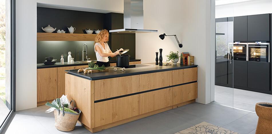 Echtholz-Küche der Serie Rocca Asteiche (PG7) mit Kochinsel und schwarzer Arbeitsplatte. Foto: Schüller Küchen