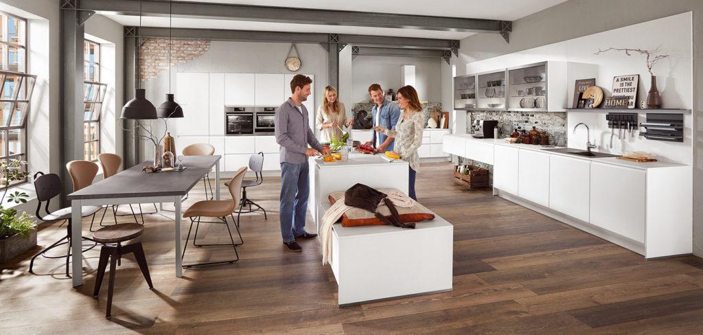 Offene Wohnküche mit großer Insel, Sitzplatz, weißen Fronten und Arbeitsplatte aus Beton; Foto: Nobilia