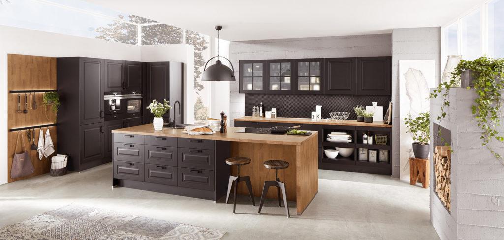 Moderne Landhausküche mit Insel aus Holz und dunklen Fronten; Foto: Nobilia