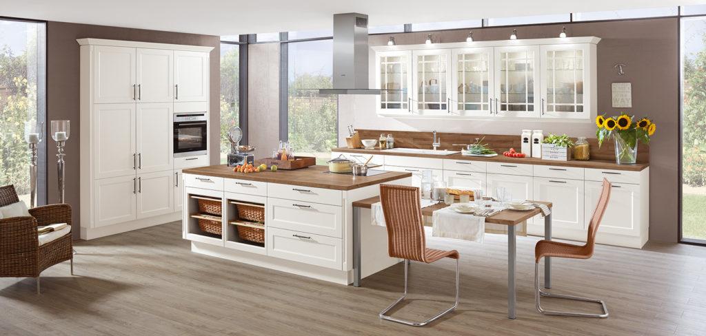 Moderne Landhausküche mit Kochinsel, weißen Küchenfronten und Arbeitsplatte aus Holz; Foto: Nobilia
