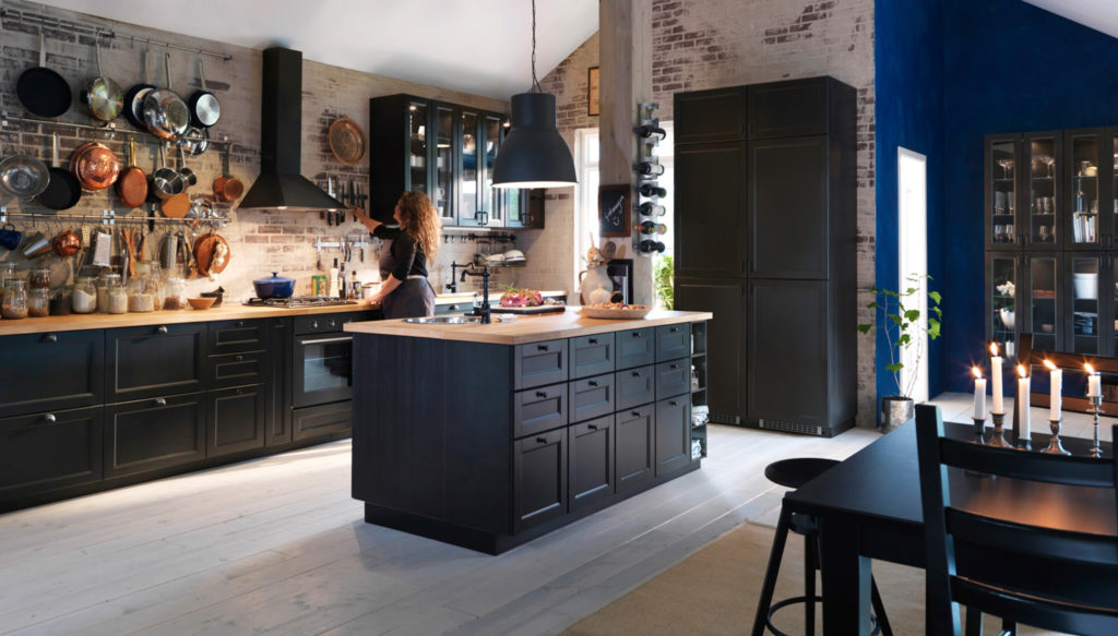 Landhausküche mit schwarzen, matten Fronten, Knopfgriffen, Kochinsel und Arbeitsplatte aus Holz