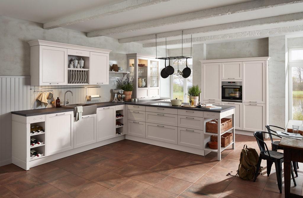 Moderne Landhausküche mit Halbinsel und schwarzer Arbeitsplatte; Foto:
