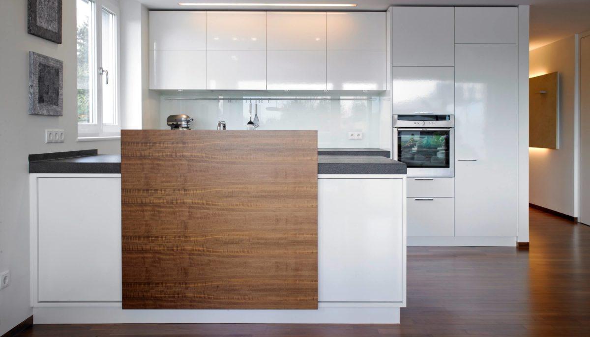 Weiße Hochglanzküche mit Halbinsel und Bar aus Holz; Planung und Umsetzung: Hase & Kramer