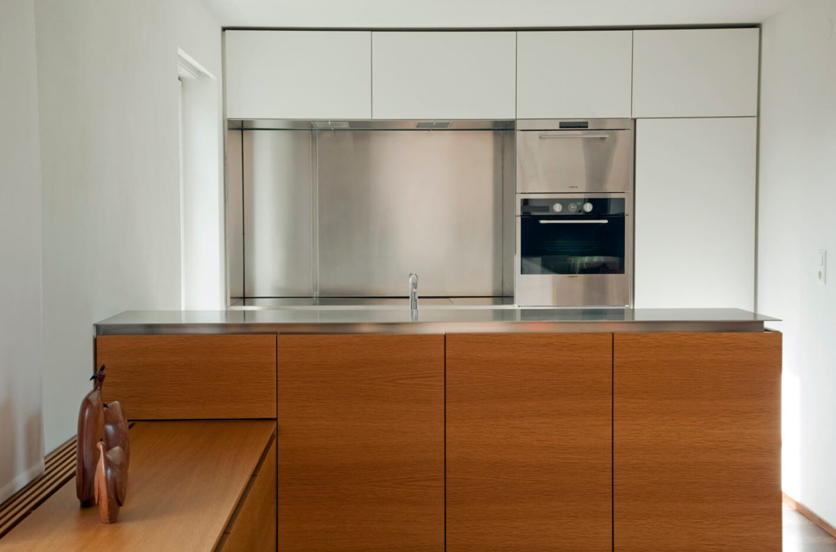 Moderne Küche mit Halbinsel aus Holz und Arbeitsplatte aus Edelstahl; Planung und Umsetzung: Hutle Dornbirn