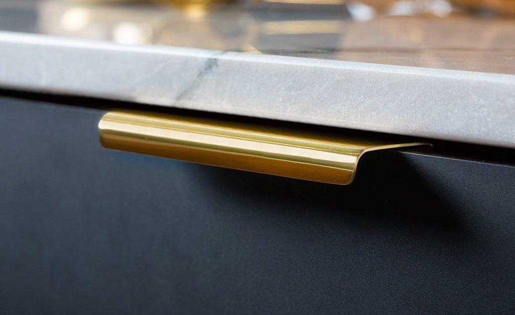 Küche mit Marmor-Arbeitsplatte und Lip Griffen in Gold; Foto: Beslag Design