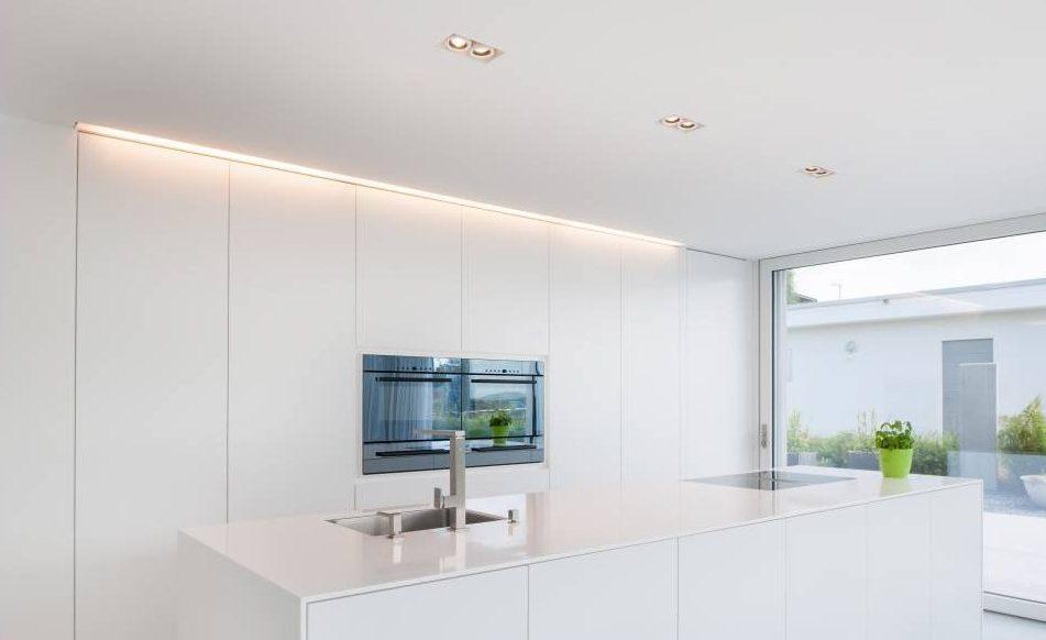 Küche mit Spots und indirekter Beleuchtung in der Decke über den Küchenschränken; Foto: Hi-Macs