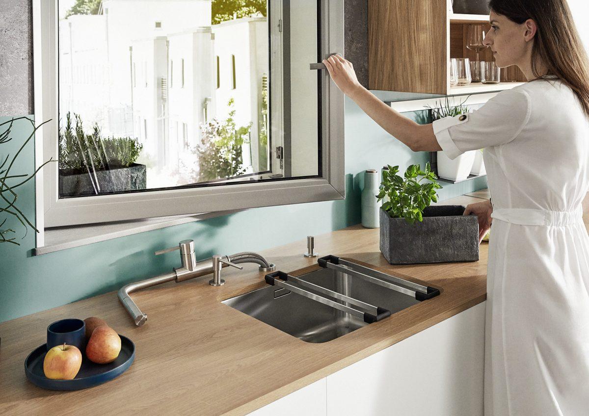 Ob Kräuter gießen, lüften oder Fenster putzen: Mit Vorfenster- Armaturen von Blanco lässt sich die Spüle direkt am Fenster planen. Lanora-S-F in gebürsteten Edelstahl macht bei Bedarf blitzschnell Platz. Foto: BLANCO