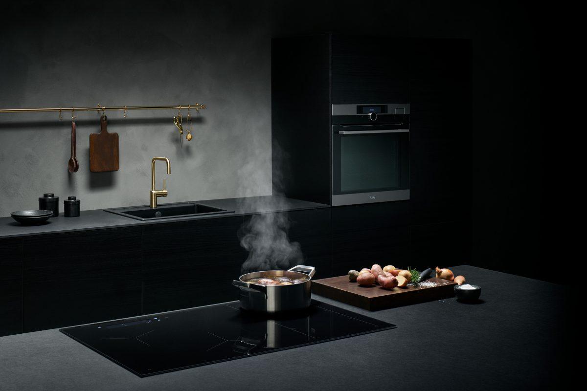 Schwarzes Kochfeld mit Abzug von AEG; Foto: AEG